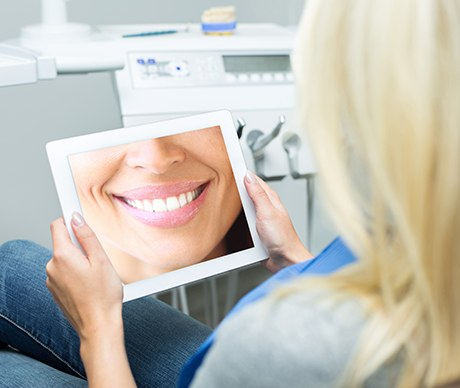 Woman looking at smile design on tablet computer