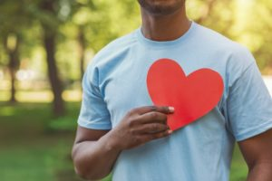 man holding a red paper heart to his chest for American Heart Month